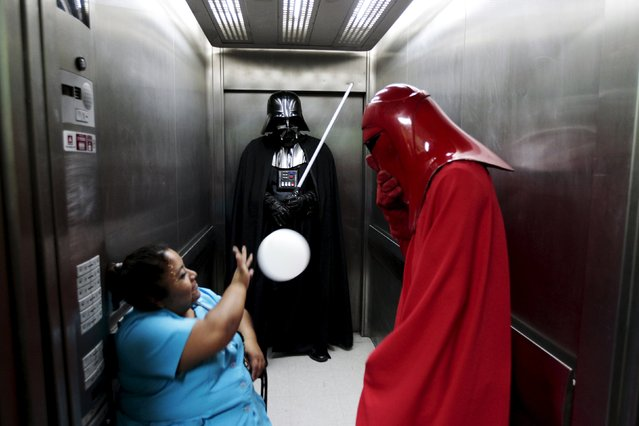 Cosplayers dressed as characters from the Star Wars movie series joke with an elevator operator during a charity event organised by the El Salvador Star Wars fan club at the Benjamin Bloom National Children's Hospital in San Salvador, El Salvador December 14, 2015. (Photo by Jose Cabezas/Reuters)