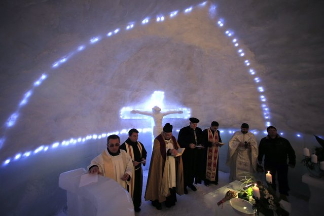 A group of priests of various congregations hold an inaugural mass for a church made entirely from ice at Balea Lac resort in the Fagaras mountains January 29, 2015. (Photo by Radu Sigheti/Reuters)