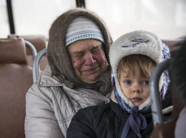 An elderly woman reacts while sitting with a child inside a bus before the departure as people flee due to a military conflict in Debaltseve, February 4, 2015. (Photo by Sergey Polezhaka/Reuters)