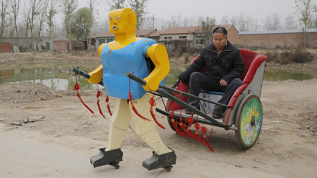 Robot inventor Wu Yulu sits on a rickshaw driven by a robot which he invented in his village in rural Beijing's Tongzhou district, China, 17 November 2016. The 54-year-old Chinese farmer living in rural Beijing's Tongzhou district invented 63 robots in the past 30 years. Wu, who only received primary school education, plans to give up the agricultural work for his robot products. He regularly participates in exhibitions, transfers patent rights and teaches at the university to earn money. (Photo by Wu Hong/EPA)