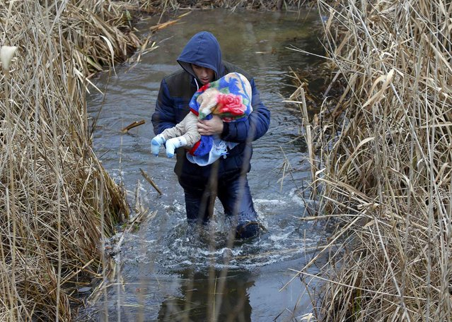 A Kosovo man carries his baby as he crosses illegally the Hungarian-Serbian border near the village of Asotthalom February 6, 2015. The European Union is experiencing a steep rise in the number of Kosovo citizens smuggling themselves into the affluent bloc, with 10,000 filing for asylum in Hungary in just one month this year compared to 6,000 for the whole of 2013. (Photo by Laszlo Balogh/Reuters)