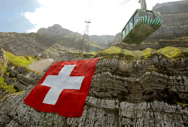 Climbers place a huge 80x80 metres (262x262 feet) Swiss national flag on the western face of the north-eastern Swiss landmark Mount Saentis, Switzerland on July 31, 2018. (Photo by Arnd Wiegmann/Reuters)