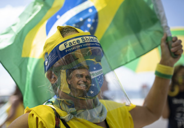 A woman wearing a face shield and mask decorated with an image of Brazilian President Jair Bolsonaro takes part in a demonstration to show support for Bolsonaro, after leaders of all three branches of the armed forces jointly resigned following the president's replacement of the defense minister, on Copacabana beach in Rio de Janeiro, Brazil, Wednesday, March 31, 2021. (Photo by Silvia Izquierdo/AP Photo)