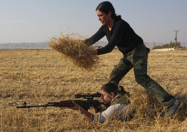 A Young Syrian-Kurdish woman hides a participant with hay in a training session organized by the Kurdish Women's Defense Units (YPJ) on August 28, 2013, in the northern Syrian border village of al Qamishli, to prepare them to defend their villages if they come under attack. (Photo by Benjamin Hiller/AFP Photo)