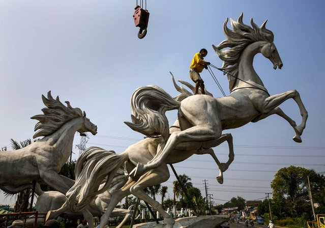 A worker tightens a rope to raise a 13 foot) statue of horses at a new housing complex at Parung village in Bogor, Indonesia's West Java, on September 19, 2013. (Photo by Beawiharta/Reuters)