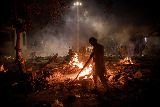 Workers can be seen at a crematorium where multiple funeral pyres are burning for patients who lost their lives to Covid-19 on April 29, 2021 in New Delhi, India. With recorded cases crossing 380,000 a day and 3000 deaths in the last 24 hours, India has more than 2 million active cases of Covid-19, the second-highest number in the world after the U.S. A new wave of the pandemic has totally overwhelmed the country's healthcare services and has caused crematoriums to operate day and night as the number of victims continues to spiral out of control. (Photo by Anindito Mukherjee/Getty Images)