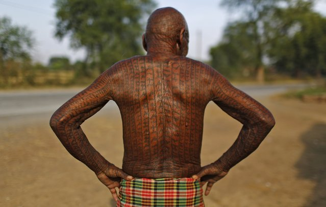 Jhingur Ram, 76, a follower of Ramnami Samaj, who has tattooed the name of the Hindu god Ram on his entire body, poses for a picture outside his house in the village of Chandai, in the eastern state of Chhattisgarh, India, November 15, 2015. (Photo by Adnan Abidi/Reuters)