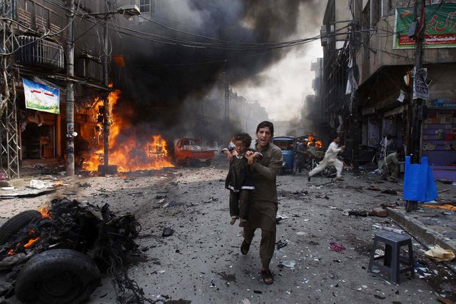 A man carrying an injured child rushes away from the site of a blast shortly after a car exploded on a crowded street in Peshawar, Pakistan, on September 29, 2013. At least 33 people were killed and 70 injured in the third blast to hit the troubled city in a week, officials said. (Photo by Mohammad Sajjad/Associated Press)