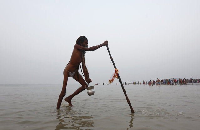 "A Sadhu or a Hindu holy man walks after taking a dip at the confluence of the river Ganges and the Bay of Bengal, ahead of the ""Makar Sankranti"" festival at Sagar Island, south of Kolkata, India, January 13, 2016. (Photo by Rupak De Chowdhuri/Reuters)"