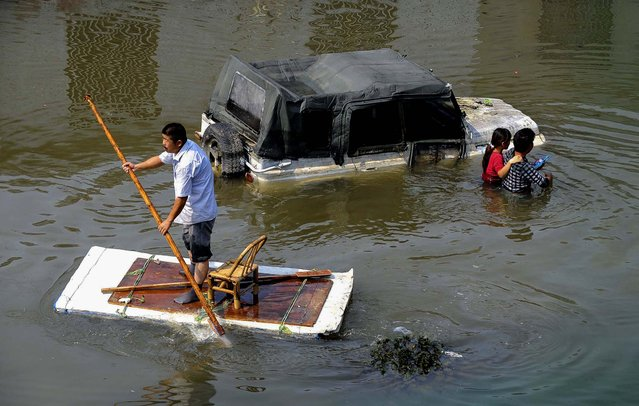 A man  paddles a makeshift raft as residents walk past a partially submerged car on a flooded street in Yuyao, Zhejiang province, on Oktober 11, 2013. Power remains cut  for the third consecutive day for tens of thousands of households in after Typhoon Fitow-triggered downpours lashed the city. (Photo by Lang Lang/Reuters)