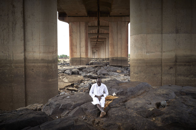 The Imam of the Mosque in Soutadounou is seen meditating under the third bridge of Bamako, during the Eid al-Fitr, the holiday that marks the end of the Holy Month of Ramadan, on May 12, 2021. (Photo by Michele Cattani/AFP Photo)