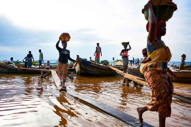 Malian women unload river sand from boats moored in the port of Bamako on September 30, 2018. (Photo by Michele Cattani/AFP Photo)