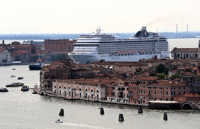 The MSC Orchestra cruise ship sails across the basin as it leaves Venice on June 05, 2021. The cruise ship, which arrived in Venice on June 03, 2021 for the first time in 17 months, signalling the return of tourists after the coronavirus pandemic but enraging those who decry the impact of the giant floating hotels on the world heritage site, picked up about 650 passengers on June 05, before heading south to sample the delights of Bari, Corfu, Mykonos and Dubrovnik. (Photo by Miguel Medina/AFP Photo)
