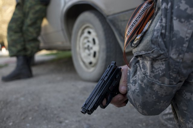 In this Saturday, March 22, 2014 file photo a pro-Russian militia member holds a pistol while Russian soldiers assault the Belbek airbase, outside Sevastopol, Crimea. (Photo by Andrew Lubimov/AP Photo)