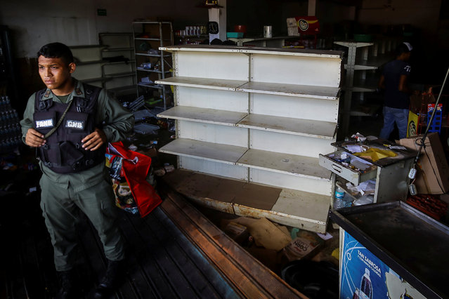 A Venezuelan National Guard stands guard as workers recover the valuables after a supermarket was looted in Ciudad Bolivar, Venezuela December 19, 2016. (Photo by William Urdaneta/Reuters)