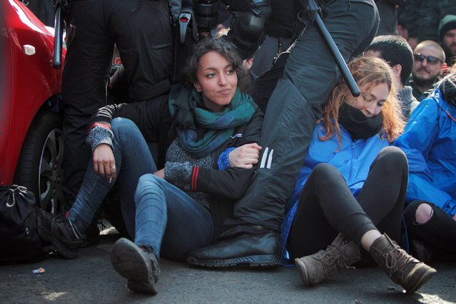 A group of protesters sit on a street amidst riot police, waiting to be marched off during the opening ceremony of the new European Central Bank (ECB) headquarter in Frankfurt, Germany, 18 March 2015. The new headquarters of the ECB officially opened on 18 March, while a demonstration by leftist protest group Blockupy was also set to take place. (Photo by Frederik von Erichsen/EPA)
