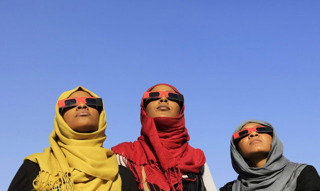 Women observe a solar eclipse during an event organized by the Sudanese Society for Astronomy and Space Science on the banks of the Nile river in Khartoum November 3, 2013. Sky watchers across the world are in for a treat Sunday as the final solar eclipse of 2013 takes on a rare hybrid form. (Photo by Mohamed Nureldin Abdallah/Reuters)