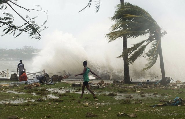 Local residents walk past debris as a wave breaks nearby in Port Vila, the capital city of the Pacific island nation of Vanuatu March 14, 2015. Winds of up to 250 kilometers an hour (155 mph) ripped metal roofs off houses and downed trees in Vanuatu on Saturday, as relief agencies braced for a major rescue operation and unconfirmed reports said dozens had already died. (Photo by Reuters/UNICEF Pacific)