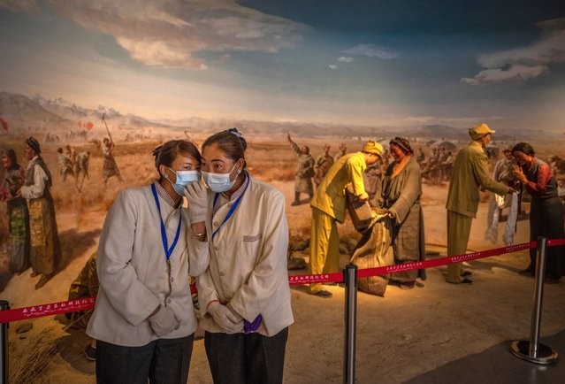 Tibetan workers chat in front of a display at the Tibet Million Serfs Memorial Hall during a government organized visit for journalists on June 1, 2021 in Lhasa, Tibet Autonomous Region, China. (Photo by Kevin Frayer/Getty Images)