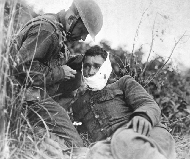 A wounded soldier, member of Company K, 110th Regimental Infantry, has a bandage wrapped aournd his face as he receives first aid treatment, Varennes-en-Argonne, France, September 1918. US Army Photo. (Photo by Interim Archives/Getty Images)