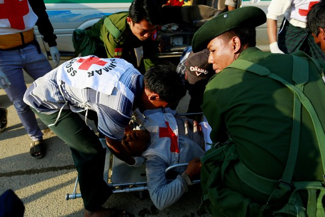 A Myanmar army soldier helps to carry Moe Kyaw Than, 45, a volunteer with the Myanmar Red Cross Society, after Than was wounded when the convoy he was in, was fired upon by the Myanmar National Democratic Alliance Army (MNDAA), according to the Myanmar army, between the capital of Kokang, Laukkai, and Chinshwehaw, February 17, 2015. (Photo by Soe Zeya Tun/Reuters)