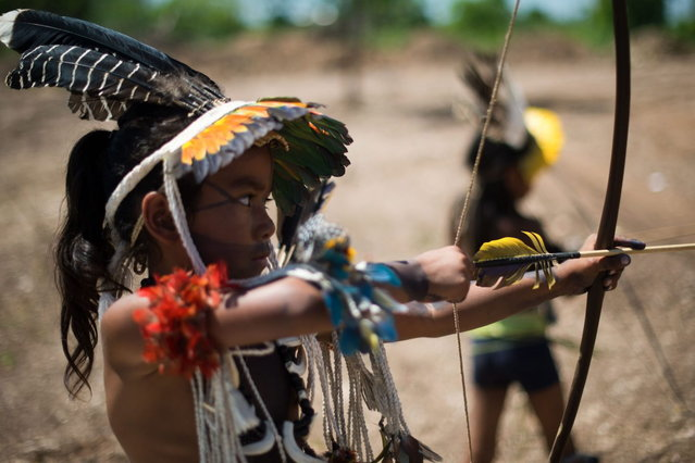 Children from the Brazilian Umutina tribe play with bows and arrows before the visit of Brazilian Sport Minister Aldo Rebelo at the XIIth Games for Indigenous People in Cuiaba, Mato Grosso state, on 13 November, 2013 Brazil. (Photo by Christophe Simon/AFP Photo)