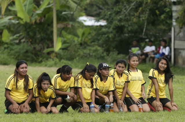 In this November 25, 2018 photo, a group of Guna women sit on the field during a penalty shootout in the women's soccer competition of the second edition of the Panamanian indigenous games in Piriati, Panama. The Guna women won the match and advanced to the semifinal and won the championship. (Photo by Arnulfo Franco/AP Photo)