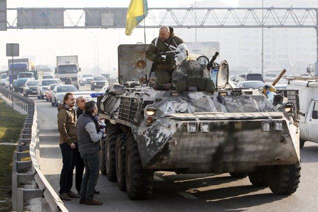 Civilians talk to Ukrainian serviceman who is returning from the front line in eastern Ukraine, in Kiev, March 11, 2015. (Photo by Valentyn Ogirenko/Reuters)