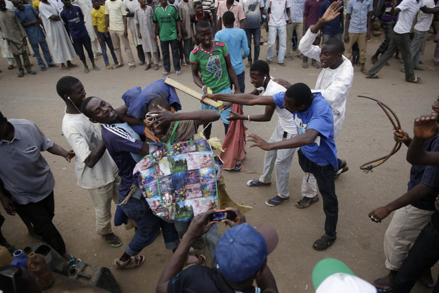 A Nigerian man carrying a dummy of President Goodluck Jonathan on his back joins others as they celebrate the anticipated victory of Presidential candidate Muhammadu Buhari  in Kaduna,  Nigeria Tuesday, March 31, 2015. (Photo by Jerome Delay/AP Photo)