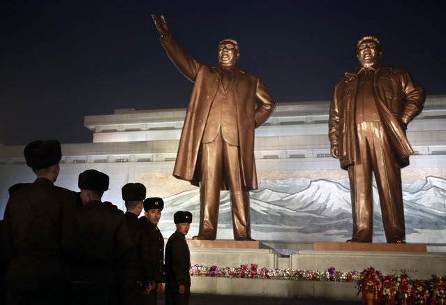 North Korean soldiers line up as they pay respect to the bronze statues of their late leaders Kim Il Sung and Kim Jong Il at Mansu Hill Grand Monument in Pyongyang, North Korea, Sunday, December 16, 2018. Many North Koreans are marking the seventh anniversary of the death of leader Kim Jong Il with visits to the statues and vows of loyalty to his son, Kim Jong Un. (Photo by Dita Alangkara/AP Photo)