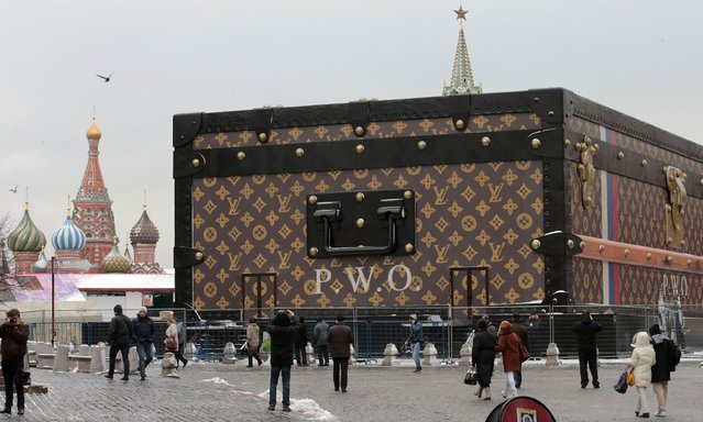People walk past a Louis Vuitton pavilion which is in the shape of a giant suitcase, as the St. Basil's Cathedral (L) and the Spasskaya Tower are seen in the background, in central Moscow, November 27, 2013. The pavilion is going to house a travel-themed exhibition. (Photo by Tatyana Makeyeva/Reuters)