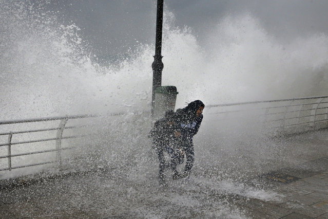 A woman and her son play as waves crash into the seawall, in Beirut, Lebanon, Sunday, January 6, 2019. A strong storm in Lebanon brought cold temperatures and snow to Lebanon's mountains and heavy rainfall, strong winds on the Lebanese coast, paralyzing parts of the Mediterranean country. (Photo by Bilal Hussein/AP Photo)