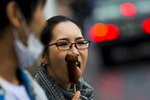 A woman eats candy in the shape of a phallus during the Kanamara Matsuri, or Iron Phallus Festival through a street near the Kanamara shrine in Kawasaki outside of Tokyo April 5, 2015. The festival celebrates fertility and is used to raise awareness and money for the prevention of sexually transmitted diseases. (Photo by Thomas Peter/Reuters)