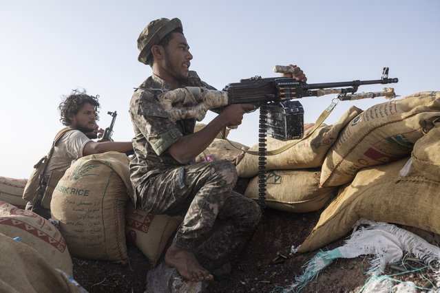 Yemeni fighter Hassan Saleh, left, identifies a target for a fighter during clashes with Houthi rebels on the Kassara front line near Marib, Yemen, Sunday, June 20, 2021. On the most active front line in Yemen's long civil war, the months-long battle for the city of Marib has become a dragged-out grind with a steady stream of dead and wounded from both sides. (Photo by Nariman El-Mofty/AP Photo)