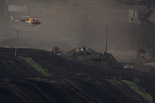 A firefighter helicopter flies over destroyed wagons at the site where a dam collapse two days prior, next to dam B6 that was at risk of breach too, in Brumadinho, Brazil, Sunday, January 27, 2019. Authorities evacuated several neighborhoods in the southeastern city of Brumadinho that were within range of the B6 dam owned by the Brazilian mining company Vale. (Photo by Leo Correa/AP Photo)