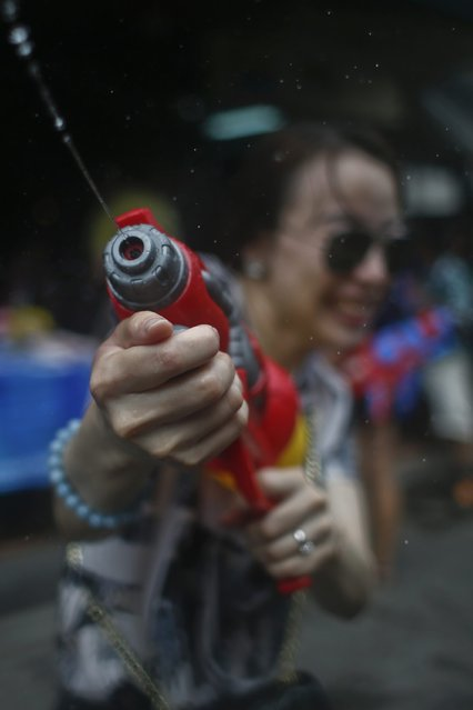 A woman takes part in a water fight as Thais and foreign tourists celebrate the water festival Songkran on the popular tourist strip of Khao San road on the first day of the water festival Songkran celebrations, the Thai traditional New Year, in Bangkok, Thailand, 12 April 2015. (Photo by Fazry Ismail/EPA)