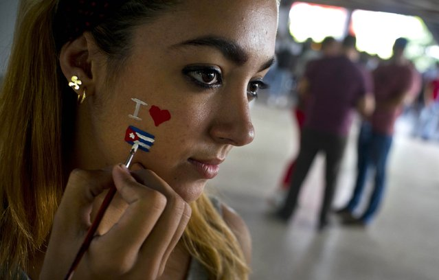 A man paints a Cuban flag on the face of a young student during an event against U.S. trade embargo against Cuba in Havana, Cuba, Wednesday, October 31, 2018. The United Nations will vote Thursday Nov. 1 on a resolution regarding the ongoing U.S. trade embargo against Cuba. (Photo by Ramon Espinosa/AP Photo)