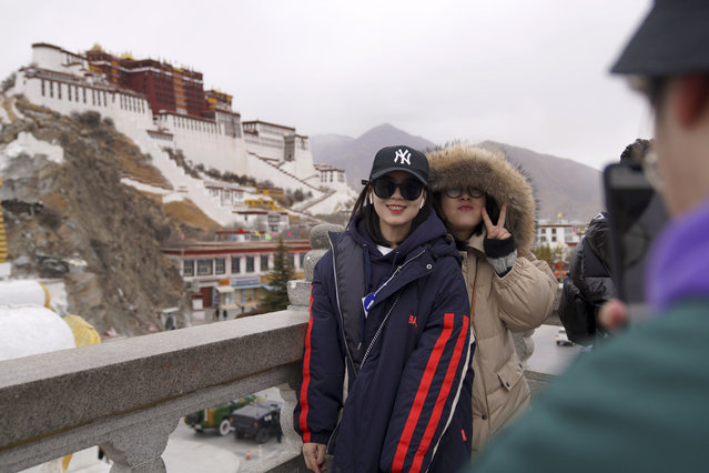 In this February 9, 2019, photo released by Xinhua News Agency, tourists pose for souvenir photos in front of the Potala Palace in Lhasa, southwest China's Tibet Autonomous Region. China is barring foreign travelers from Tibet over a period of several weeks that includes a pair of sensitive political anniversaries. Travel agencies contacted Wednesday, Feb. 20 said foreign tourists would not be allowed into the Himalayan region until April 1. (Photo by Jigme Dorje/Xinhua News Agency via AP Photo)