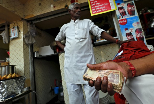 A street side restaurant owner holds a bundle of Indian currency notes as he stands outside his restaurant in New Delhi, India, February 29, 2016. India unveiled a fire-fighting budget on Monday that seeks to win back support among rural voters for Prime Minister Narendra Modi's government and sustain growth against a grim global backdrop – all without borrowing more. (Photo by Adnan Abidi/Reuters)