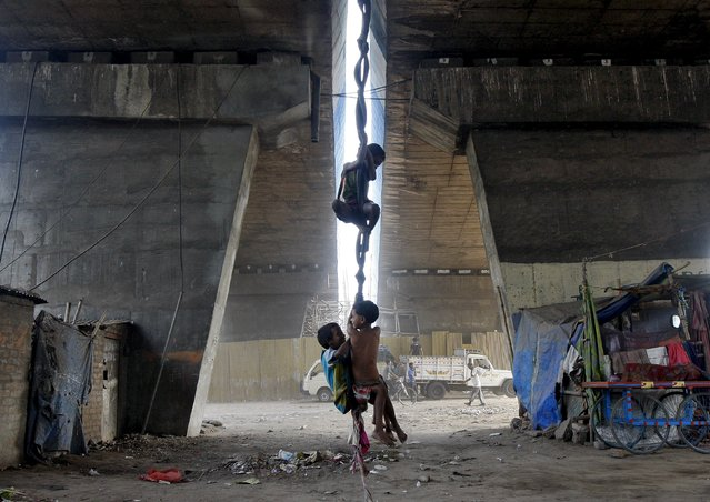 Children play on an improvised swing made of used bicycle tyres and cloth suspended from a flyover in Kolkata April 23, 2015. (Photo by Rupak De Chowdhuri/Reuters)