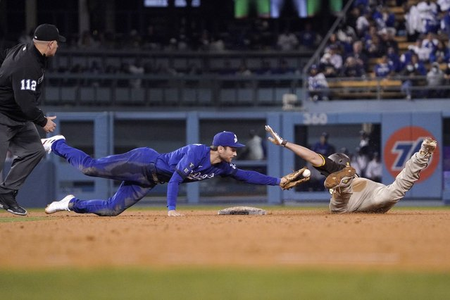 San Diego Padres' Eric Hosmer, right, slides in for a double as Los Angeles Dodgers second baseman Trea Turner, center, attempts to tag him while second base umpire Jeremy Riggs watches during the seventh inning of a baseball game Tuesday, September 28, 2021, in Los Angeles. (Photo by Mark J. Terrill/AP Photo)