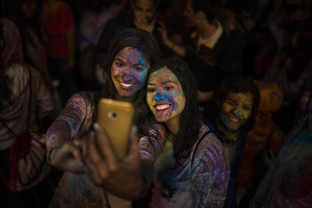 Revelers take a selfie during a Holi Festival in Madrid, Spain, Sunday, April 26, 2015. The festival is based on the Hindu spring festival Holi, also known as the festival of colours where participants colour each other with dry powder and coloured water. (Photo by Andres Kudacki/AP Photo)
