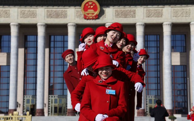 Chinese bus ushers pose for photos outside the Great Hall of the People during a plenary session of the National People's Congress held in Beijing, China, Tuesday, March 12, 2019. The country's top judge and head prosecutor delivered reports to the nearly 3,000 members of the ceremonial legislature on their accomplishments over the past year in curbing crime and prosecuting wrong doers, along with their plans for the year ahead. (Photo by Ng Han Guan/AP Photo)