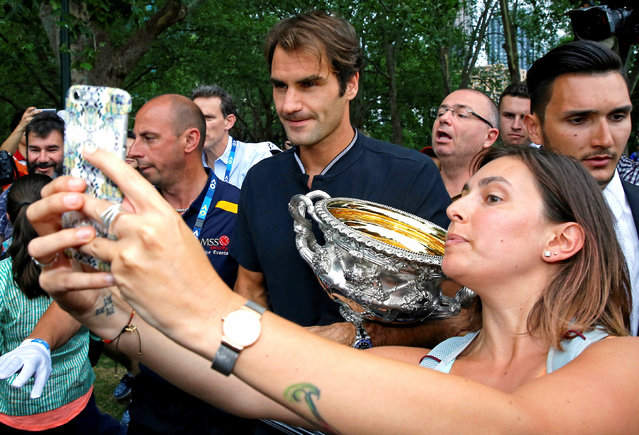A woman takes a selfie with Switzerland's Roger Federer as he holds the trophy during a photo call the morning after he won the Men's singles final at the Australian Open tennis tournament in Melbourne, Australia, January 30, 2017. (Photo by Issei Kato/Reuters)