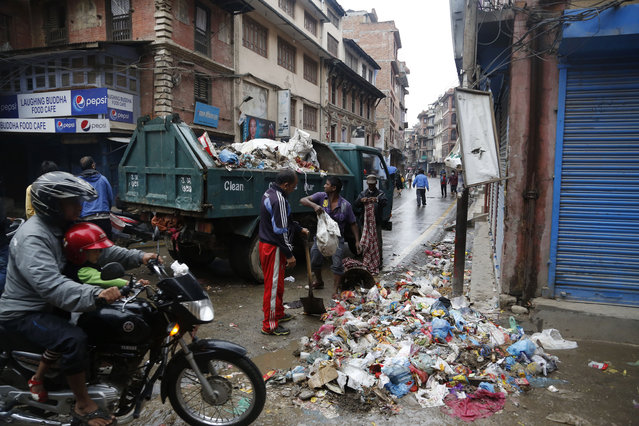 Kathmandu municipal workers collect garbage from the city in Kathmandu, Nepal, Thursday, April 30, 2015. (Photo by Manish Swarup/AP Photo)