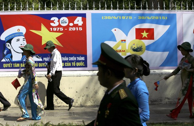 """Vietnamese walk past propaganda banners following a parade celebrating the 40th anniversary of the end of the Vietnam War which is also remembered as the """"Fall of Saigon"""", in Ho Chi Minh City, Vietnam, Thursday, April 30, 2015. (Photo by Dita Alangkara/AP Photo)"""