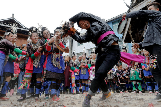 "An ethnic ""Kam"" (also known as Dong) man pulls a live chicken during a traditional wedding ritual known as the ""steal the chicken at the drum tower"" in a minority Dong village in southwestern Chinese city of Congjiang, Guizhou province, China January 29, 2017. A village in southwest China staged a traditional wedding ritual that pits ancient traditions against modern views on animal welfare in a fast changing country. The ceremony held in the ethnic Kam minority village of Gantuan in Guizhou province is based on a tradition dating back some 500 years that was revived and modified in the 1990s for villagers and tourists. The event, known locally as ""steal the chicken at the drum tower"", involves young men competing to be the first to tear apart live birds carried on poles by new brides into the village centre. (Photo by Tyrone Siu/Reuters)"