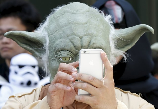 A cosplayer dressed up as Star Wars character Yoda looks at a mobile phone at a Star Wars Day fan event in Tokyo May 4, 2015. (Photo by Toru Hanai/Reuters)