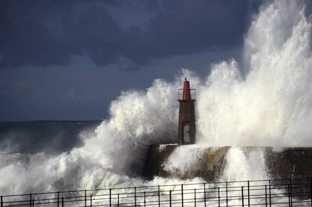 Waves crash against a lighthouse in Viavelez, northern Spain, January 21, 2015. (Photo by Eloy Alonso/Reuters)
