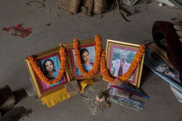 From left to right, portraits of victims of the April 25 earthquake San Nanin Pandit, 40, and her children Sita Pandit, 20, and Samir Pandit, 18, are decorated with marigold garlands as family members mark the twelfth day of their death in a mourning room in Kathmandu, Nepal, Wednesday, May 6, 2015. (Photo by Bernat Amangue/AP Photo)